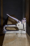 A building stapler on the boards. Construction of a frame house. Hand tool stock image