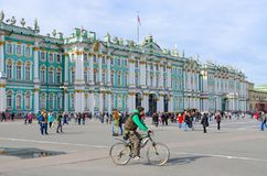 Building of State Hermitage Winter Palace, Palace Square, St. Petersburg, Russia. SAINT PETERSBURG, RUSSIA - MAY 1, 2017: Unknown people walk along Palace Square Royalty Free Stock Photo