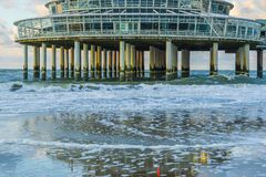 Building on stone weathered poles at the beach of scheveningen with waves in the sea and reflection in the wet sand. A building on stone weathered poles at the royalty free stock image