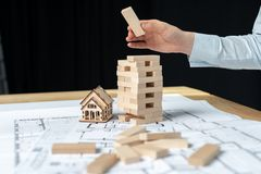 Building strategy concept. Confident architect lady in her formalwear standing indoor workroom. She holding jenga blocks in hand. Build new flat or apartment royalty free stock photography
