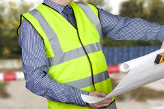 Building surveyor in hi vis checking site plans holding spirit level Royalty Free Stock Photo