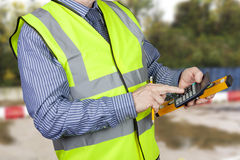 Building surveyor in hi vis vest with calculator and spirit level Stock Photo