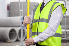 Building surveyor in high visibility adjusting tripod stand Royalty Free Stock Photography