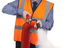 Building Surveyor in orange visibility vest using a fire extinguisher. Isolated on a white background royalty free stock images