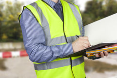 Building surveyor with sprit level writing notes in his folder stock images