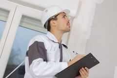 Building surveyor writing on clipboard on construction site stock image