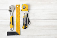 Building tools including centimeter ruler, wrench and cutter placed in the right side on wooden surface with open space. Royalty Free Stock Photos