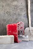 Building tools old, dirty shovel , red bucket, bricks on the gray concrete background. Copy space. Top view. stock image