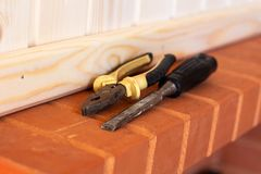 Building tools. Pliers and chisel on red brick. Close up royalty free stock photography