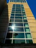 Building Tower With Sun Reflection On The Geometric Shaped Windows. Skyscraper building with many glass windows shaped in a geometric pattern stands high with a royalty free stock photo