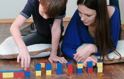 Building a towers from blocks and cubes. Mom and son playing together with wooden colored education toy blocks lying on. The floor royalty free stock image