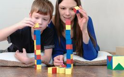 Building a towers from blocks. Mom and son playing together with wooden colored education toy blocks lying on the floor. stock photo