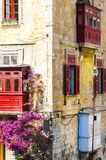Building with traditional colorful maltese balcony. In historical part of Valletta. Red windows decoreted with begonville on the facade of a house in Malta Royalty Free Stock Photography