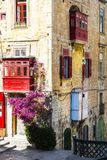 Building with traditional colorful maltese balcony. In historical part of Valletta. Red windows decoreted with begonville on the facade of a house in Malta Royalty Free Stock Photo