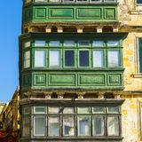 Traditional maltese balcony. Building with traditional colorful maltese balcony in historical part of Valletta. Windows on the facade of a house in Malta Royalty Free Stock Images