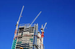 Building under construction. With big cranes over a clean blue sky background in London downtown, UK - Great Britan Royalty Free Stock Photography
