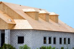 Building under construction. New building under construction showing plywood roof sheeting and three dormers Royalty Free Stock Image