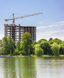 Building under construction on the bank of big lake Royalty Free Stock Images