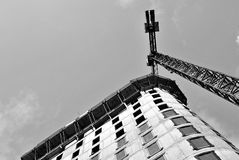 Building under construction.Black and white. High-rise building under construction. The site with cranes against blue sky Royalty Free Stock Images