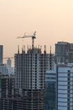 Building under construction. In business area on evening Stock Photo