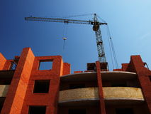 Building under construction with crane. Multistory building from brick under construction with no roof and construction crane stock images