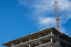 Building under construction and crane. On a background of blue sky with clouds Stock Photos