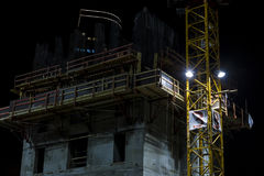 Building under construction with crane mast at night side Royalty Free Stock Images