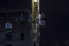 Building under construction with crane mast at night Stock Photography