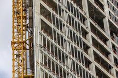 Building under construction with crane mast Stock Photos