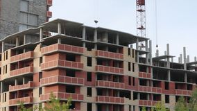 Building under construction with crane. At summer day stock video footage