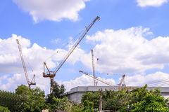Building under construction and cranes against blue sky Royalty Free Stock Images