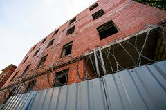 Building under construction with a fence and barbed wire. A brick building under construction with a fence and barbed wire Stock Images