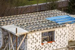 Building under construction. Roof beams frame and roofing underlayment, water-resistant waterproof barrier on walls of hollow foam. Insulation blocks. Masonry stock photo
