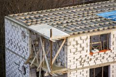 Building under construction. Roof beams frame and roofing underlayment, water-resistant waterproof barrier on walls of hollow foam. Insulation blocks. Masonry royalty free stock images