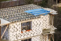 Building under construction. Roof beams frame and roofing underlayment, water-resistant waterproof barrier on walls of hollow foam. Insulation blocks. Masonry royalty free stock image