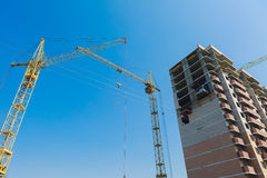 Building under construction site. Building under construction. The site with cranes against blue sky Stock Photography