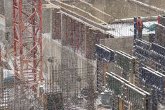 Building under construction in a snowfall. Worker stands on the edge of a concrete structure royalty free stock photo