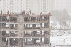 Building under construction in a snowfall. Workers on construction site stock images