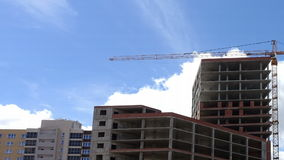Building under construction and Tower crane. On a background of flying by clouds and blue sky. Tower crane makes a slight turn stock footage