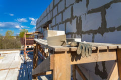 The building under construction, trowel with  concrete and working glove on the foreground Royalty Free Stock Photos