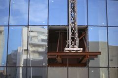 Building under construction with open in its glass wall.  Royalty Free Stock Photo