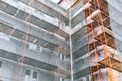 Building under construction wrapped in green net Royalty Free Stock Photo