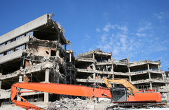 Building under demolition. With heavy machinery Royalty Free Stock Photo