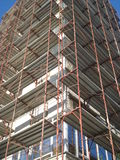 Building under rehabilitation with walls covered by metal scaffolds Royalty Free Stock Image