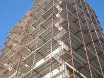Building under rehabilitation with walls covered by metal scaffolds Stock Photo