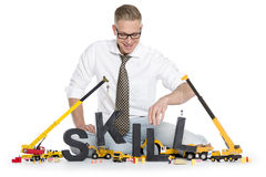 Developing skills: Businessman building skill-word. Building up skills concept: Joyful businessman building the word skill along with construction machines Royalty Free Stock Images