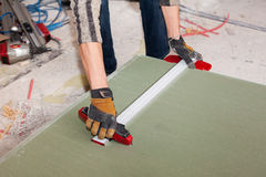 Building a wall for frame house. Worker cuts drywall. stock images