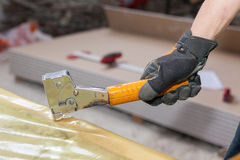 Building a wall for frame house. Worker installing vapor barrier film with staple gun. Building a wall for frame house. Worker installing vapor barrier film stock image