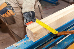 Building a wall for frame house. Worker make marks for cutting timber. Royalty Free Stock Images