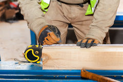 Building a wall for frame house. Worker make marks for cutting timber. Stock Photos